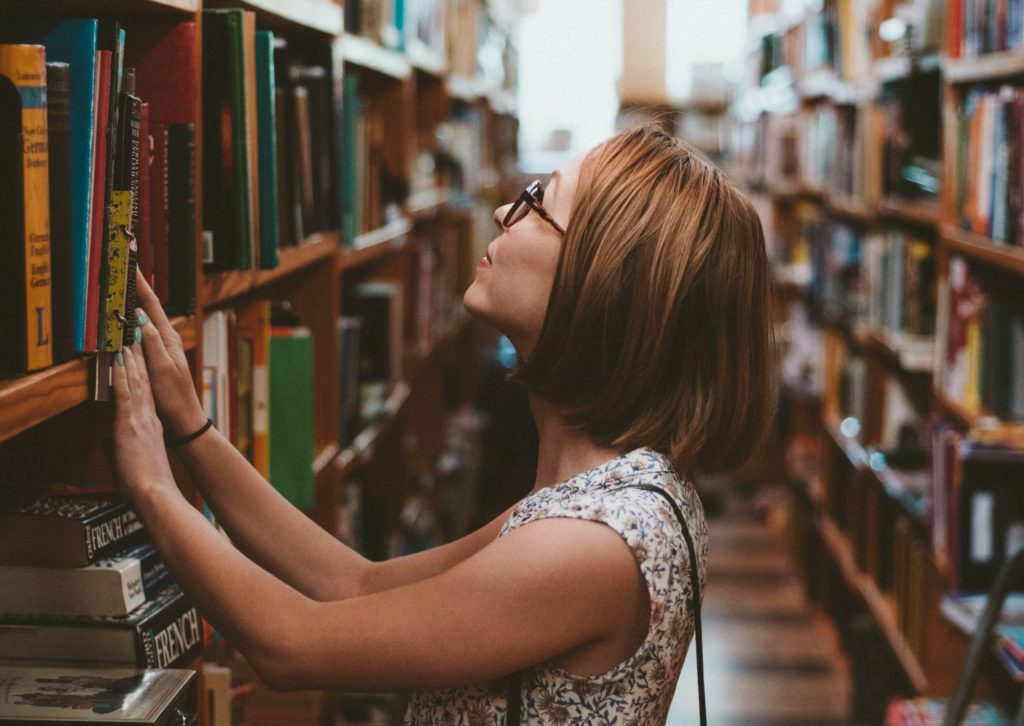 Brown hair lady in white dress looking for a book on a shelf