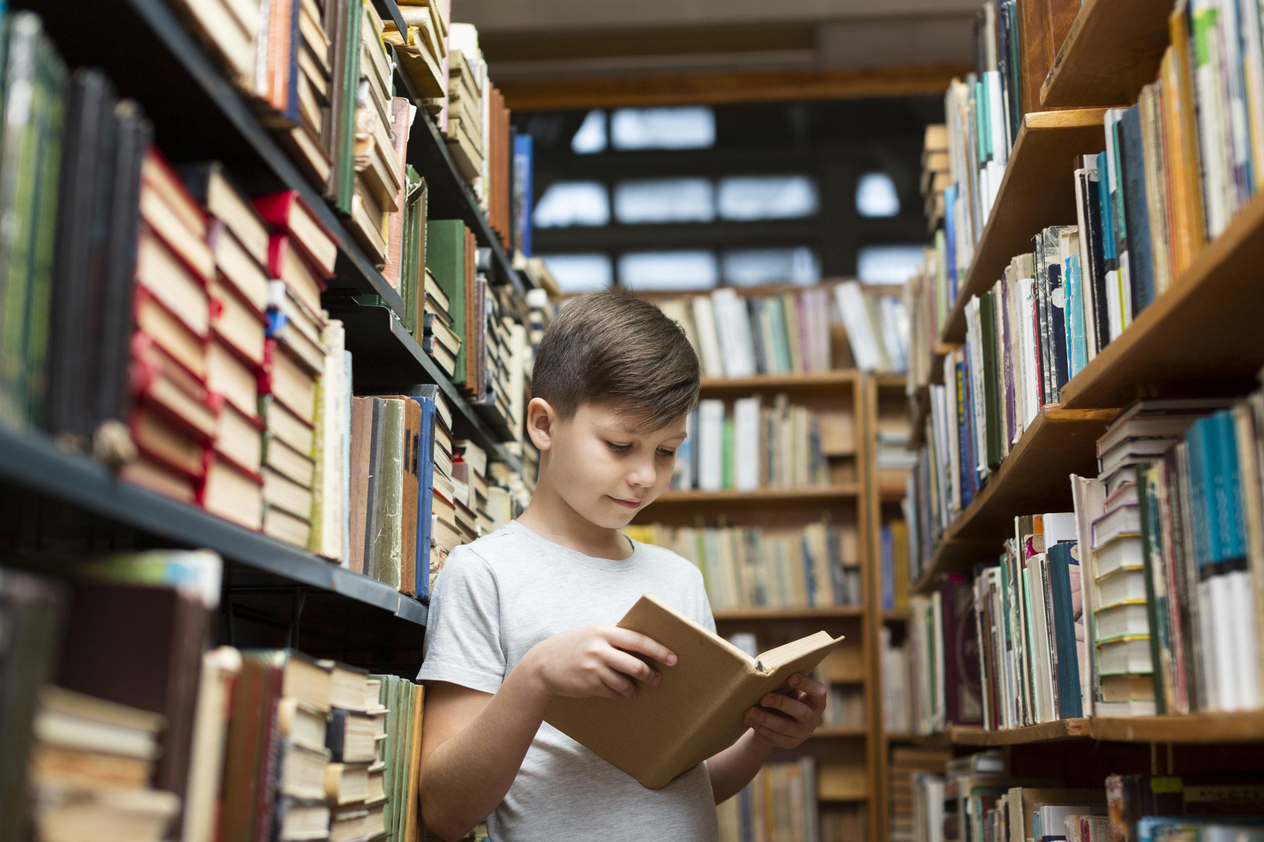 Dječak čita knjigu u knjižnici između polica
